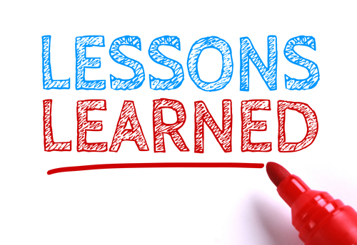 Text Lessons learned with red marker aside is isolated on white paper background.